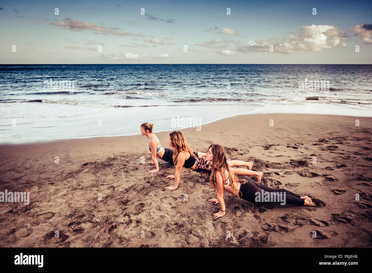 Drei junge Damen tun cacuasian Pilates am Ufer in der Nähe der Wellen und das Meer. Outdoor Freizeit Sport und Lifestyle Fitness für Wunder Stockbild