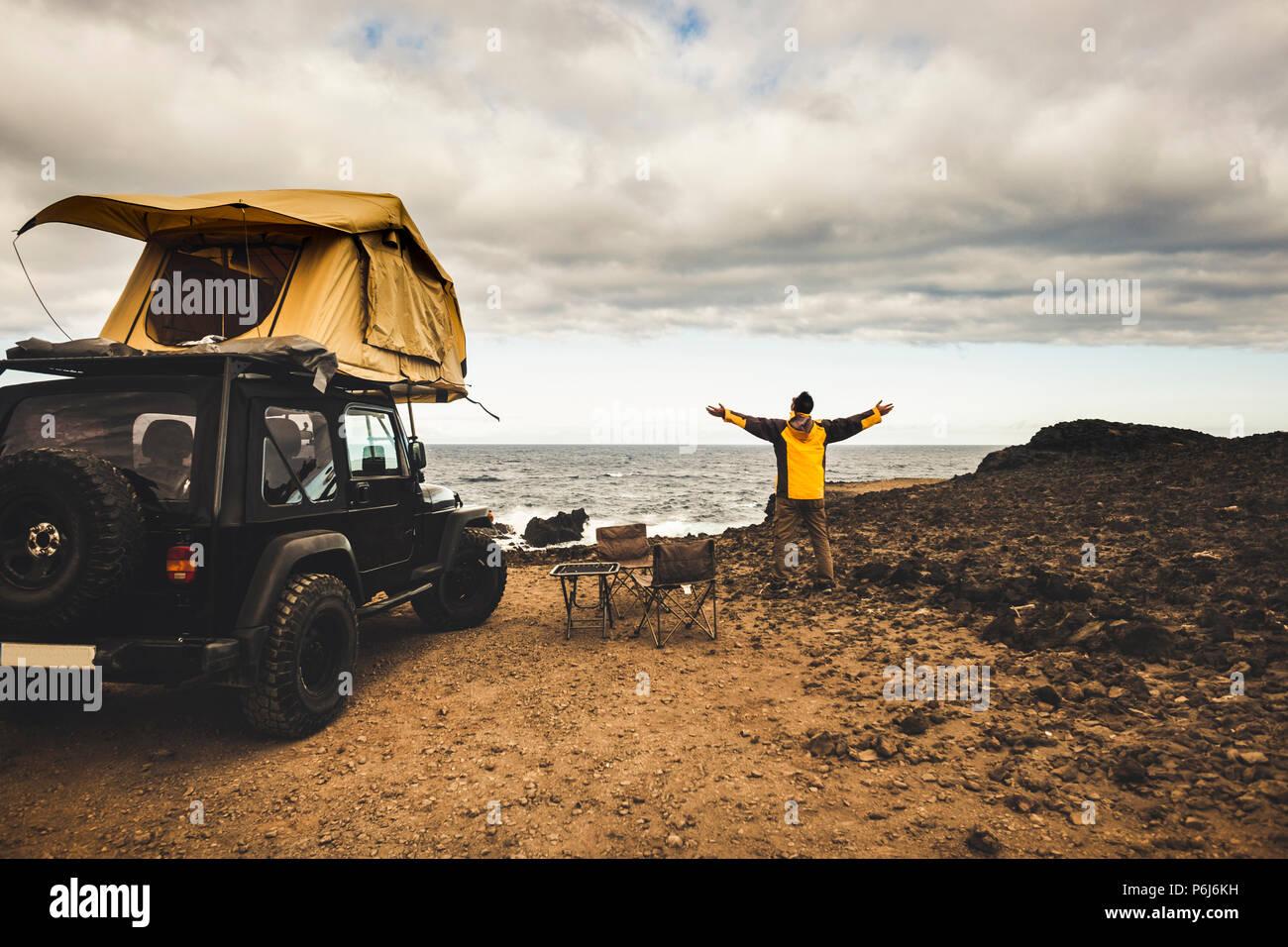 Abenteurer Mann in Reise mit off road Auto und Dachzelt Freiheit und Explorer Konzept zu genießen. Die Welt leben in der Nähe der Macht der Th entdecken Stockbild