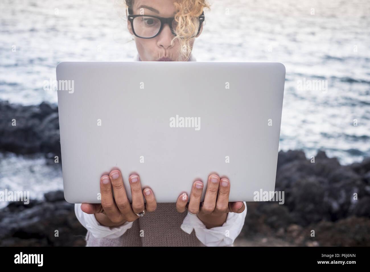 Überrascht Gesichtsausdruck für schöne kaukasischen junge Frau die Arbeit an einem Laptop in alternative office Outdoor an der Küste in der Nähe von den Wellen des Ozeans. di Stockbild