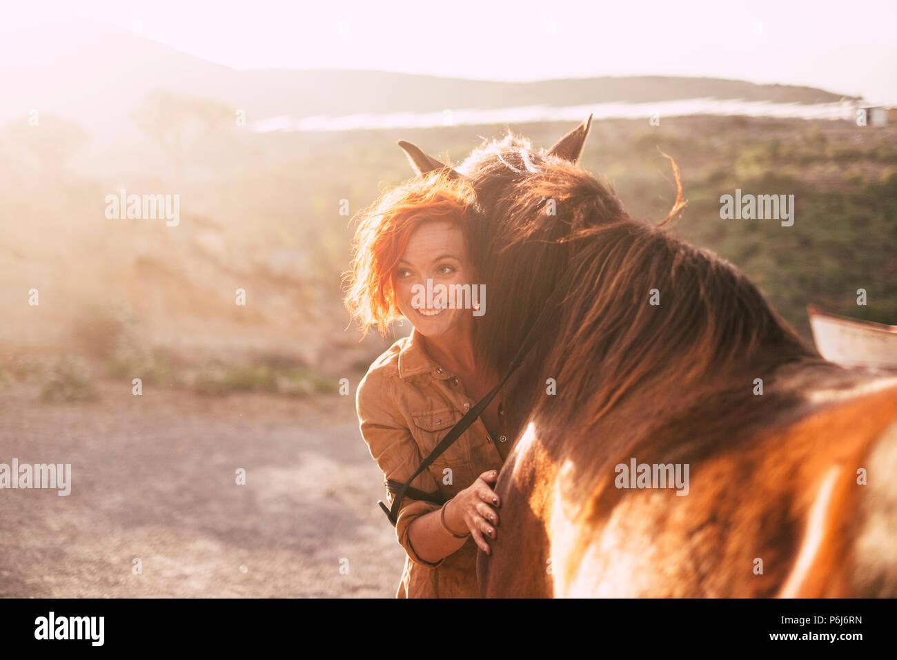 Rote Haare schöne alternative Dame Hug Ihre besten Freunde Tier Pferd in den Sonnenuntergang auf dem Land. Hintergrundbeleuchtung im Hintergrund und Liebe Konzept, Stockbild