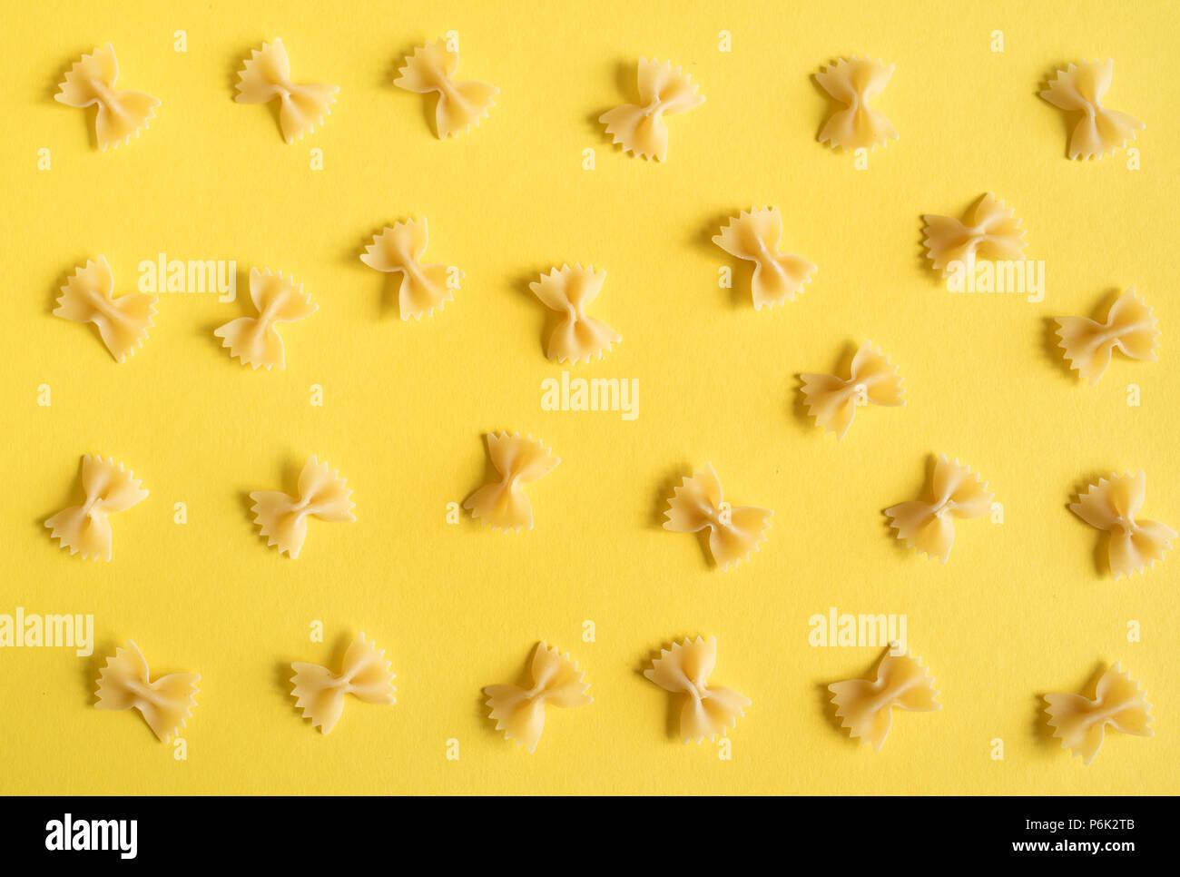 Farfalle Pasta auf gelbem Hintergrund, Ansicht von oben, flach. Stockfoto