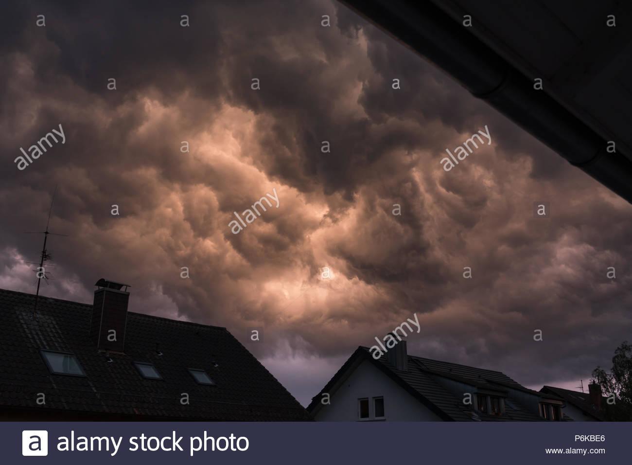 Dunkle beeindruckende Gewitterwolken über ein Dorf mit kurzen und starken Naturschauspiel während Stom. Stockbild