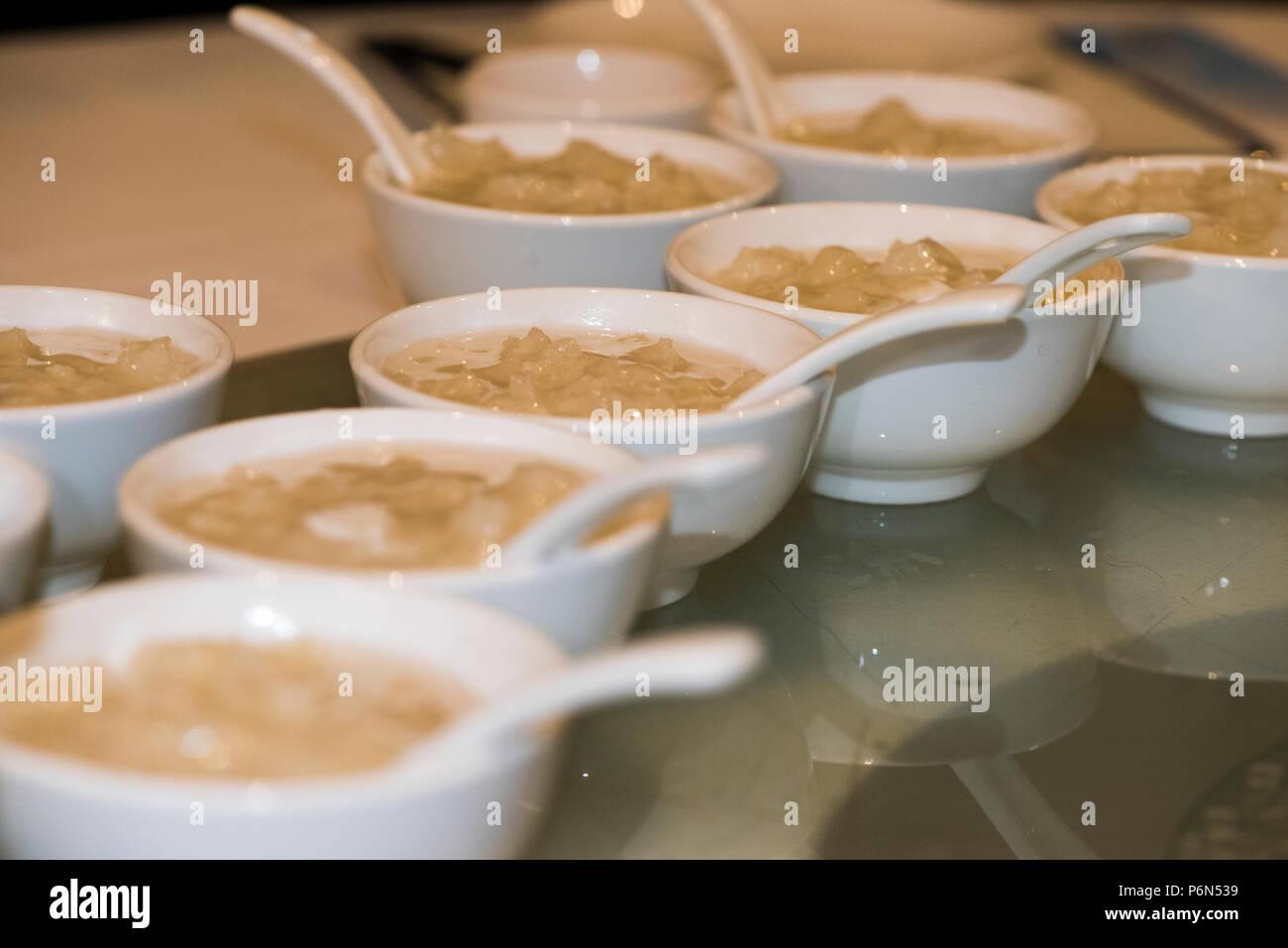 Einzelne Portionen chinesische Suppe in kleinen weißen Schale (s), mit sppon Stockbild
