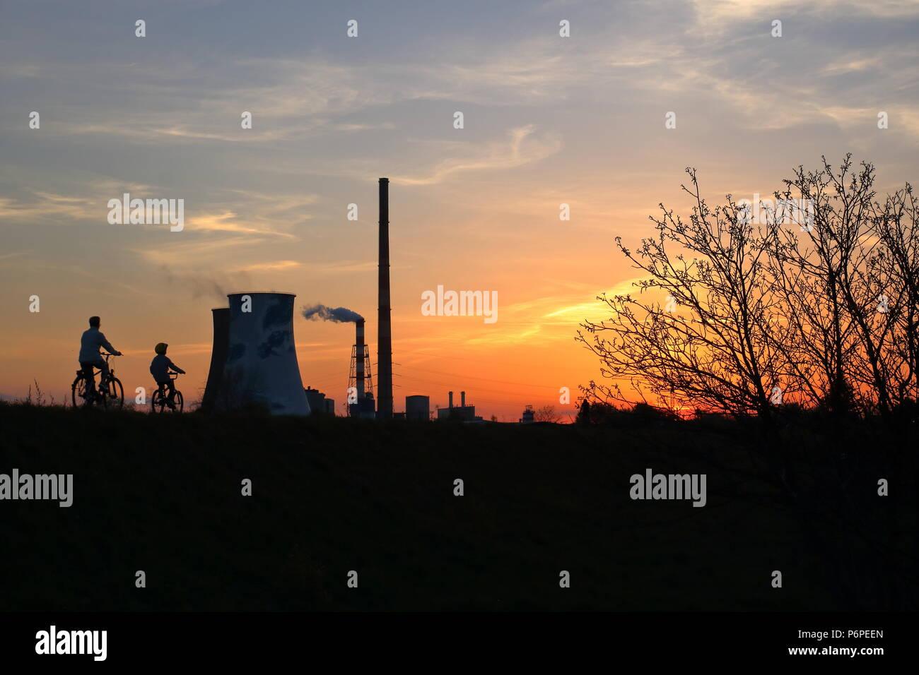 Sonnenuntergang, ornage Sky, in der Dämmerung Baum, Radweg mit zwei Radfahrer, paretna und Kinder, Gruppe von hohen und großen smkoe chimeys, von Ihnen Stockbild