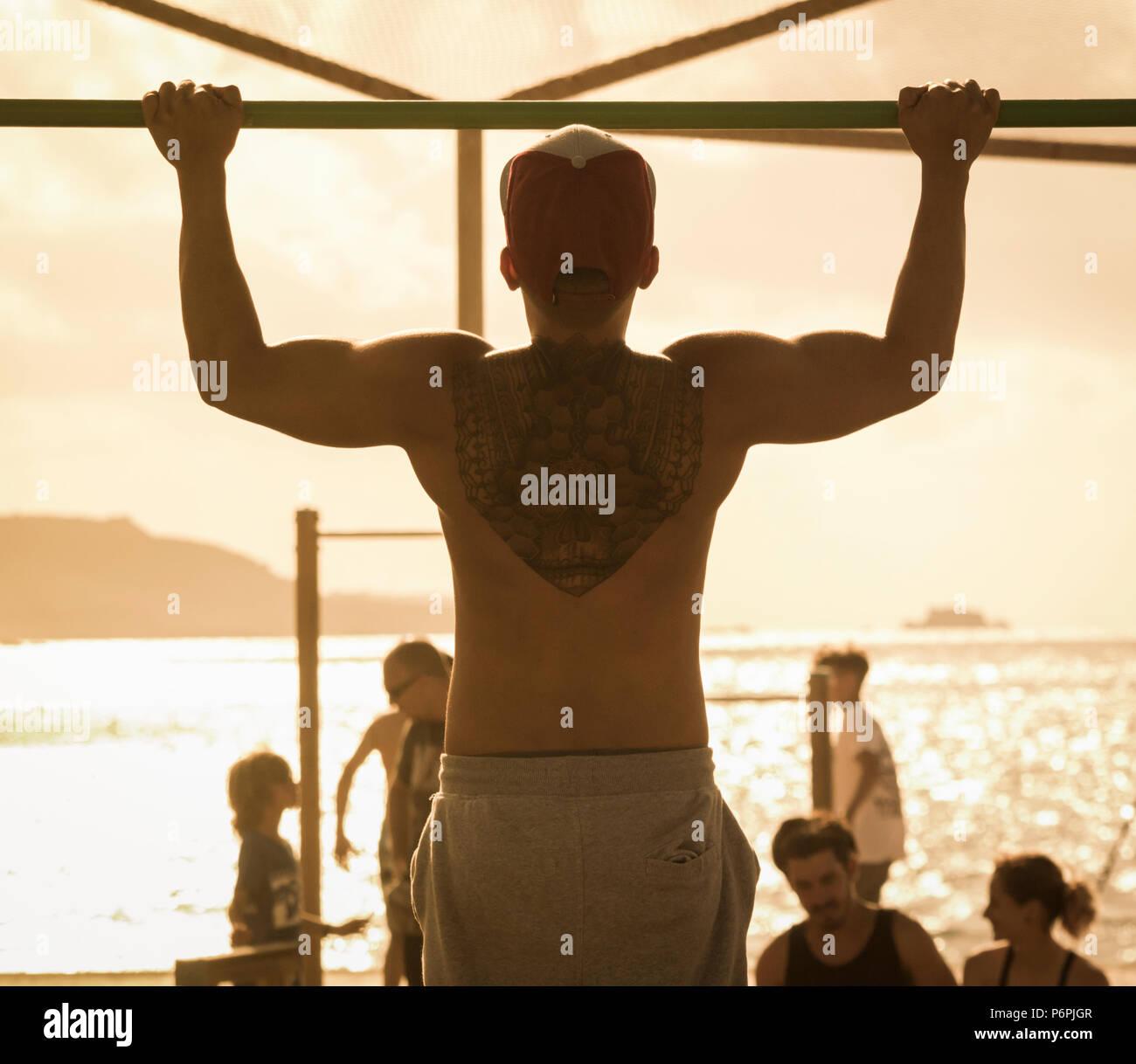Ansicht der Rückseite des muskulösen Mann mit Zurück tattoo Zug tut ups/Chin ups am Strand in Spanien Stockbild