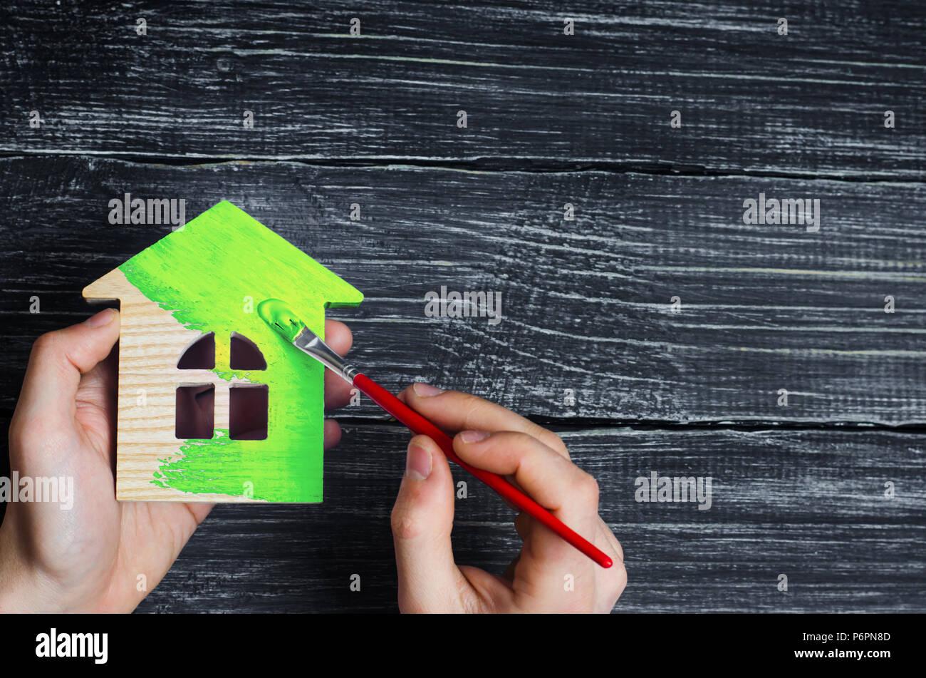 Des Menschen Hand malt die Holzhaus im grünen Pinsel. Reparatur und Renovierung des Hauses, umweltfreundliche Haus. Energieeffizienz und Quali Stockbild