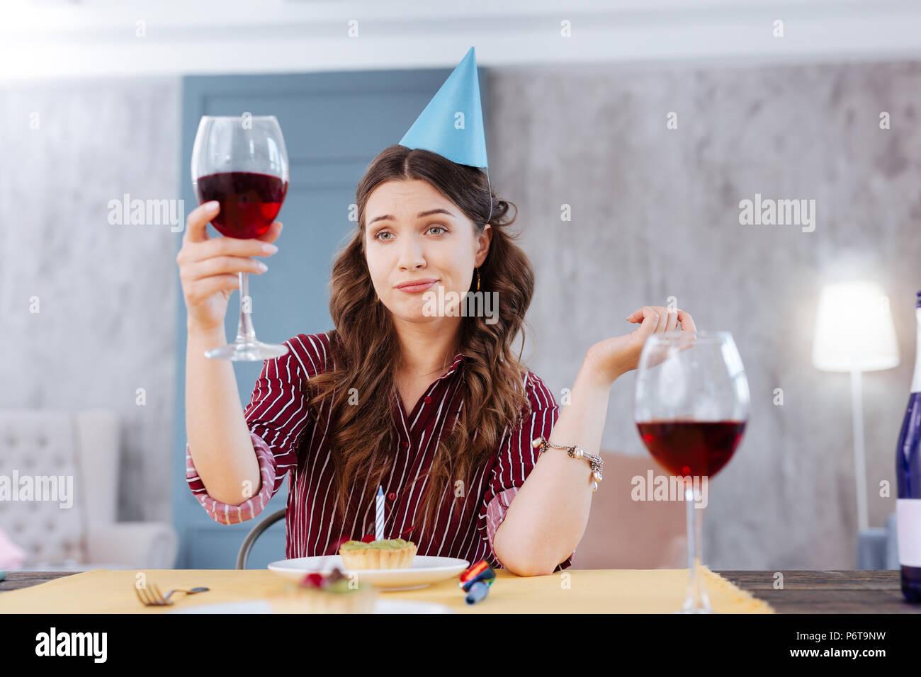 Frau, die lustiges Gesicht während der Teilnahme an Geburtstagsfeier Stockbild