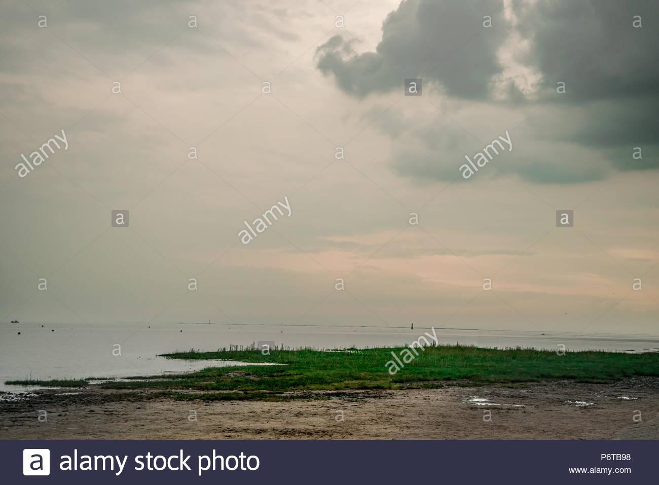 Bedeckter Himmel am Nordseestrand bei athmosphärischem Abenddämmerung mit Blick auf den Horizont. Stockbild