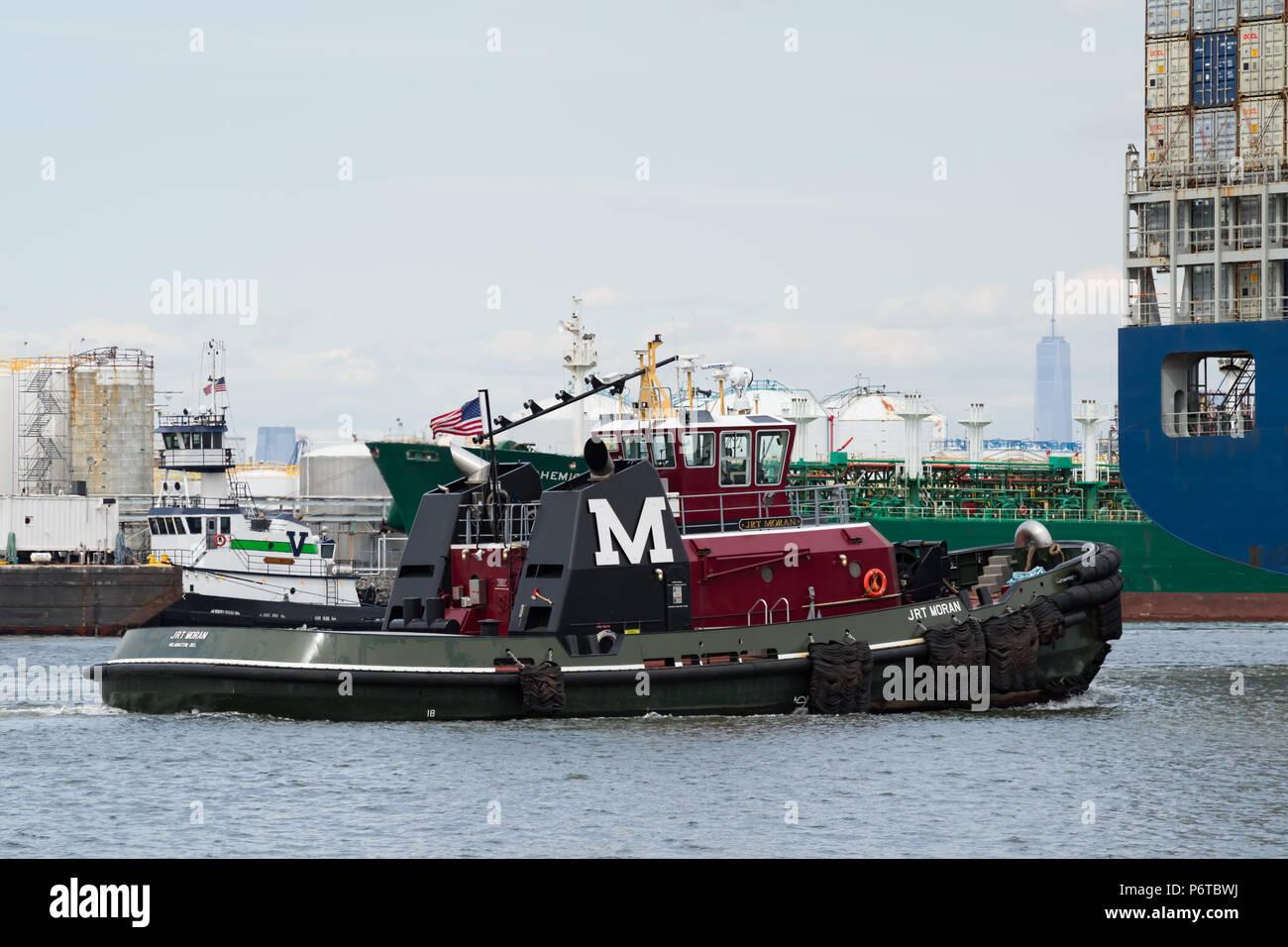 Moran Abschleppen des Traktors tug JRT MORAN eskortieren einen Container schiff entlang der geschäftigen Kill Van Kull Osten in den Hafen von New York. Freedom Tower im Hintergrund. Stockfoto