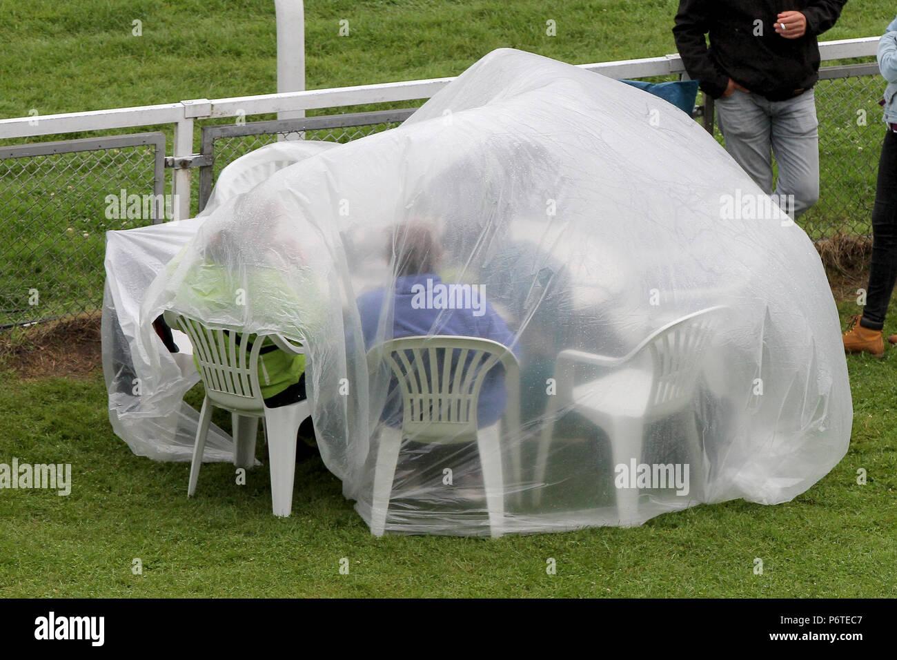 Hamburg, die Zuschauer sitzen im Regen unter einer Plastikplane, an ihrem Tisch auf der Flucht Stockbild