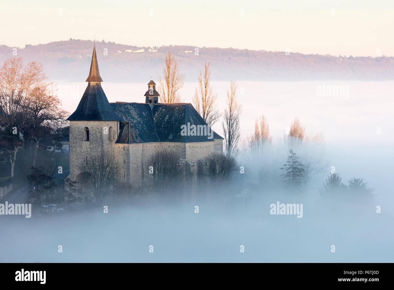 Collégiale Notre Dame et St. Pantaléauf de Turenne im Nebel bei Sonnenuntergang, Correze; Nouvelle-Aquitaine ; Frankreich ; Stockbild