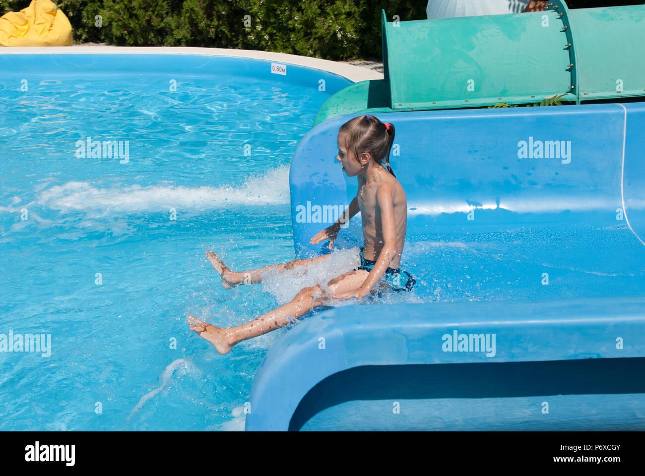 Lustige kleine dünne Mädchen auf Wasserrutsche im