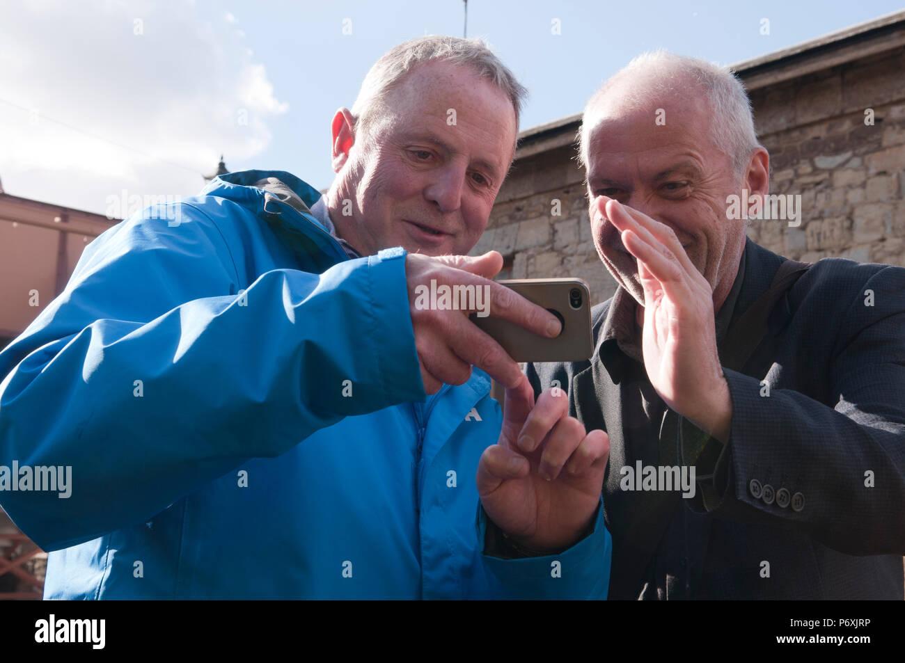 In der Nähe von zwei Männer mittleren Alters auf ein Handy suchen Lächeln Stockbild