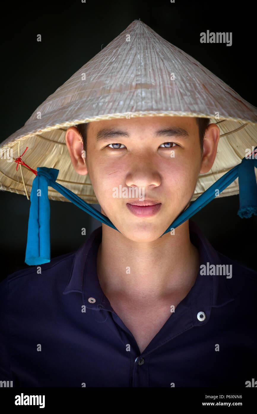 Porträt eines jungen Mannes mit traditionellen konischen Hut in Can Tho, Vietnam Stockbild