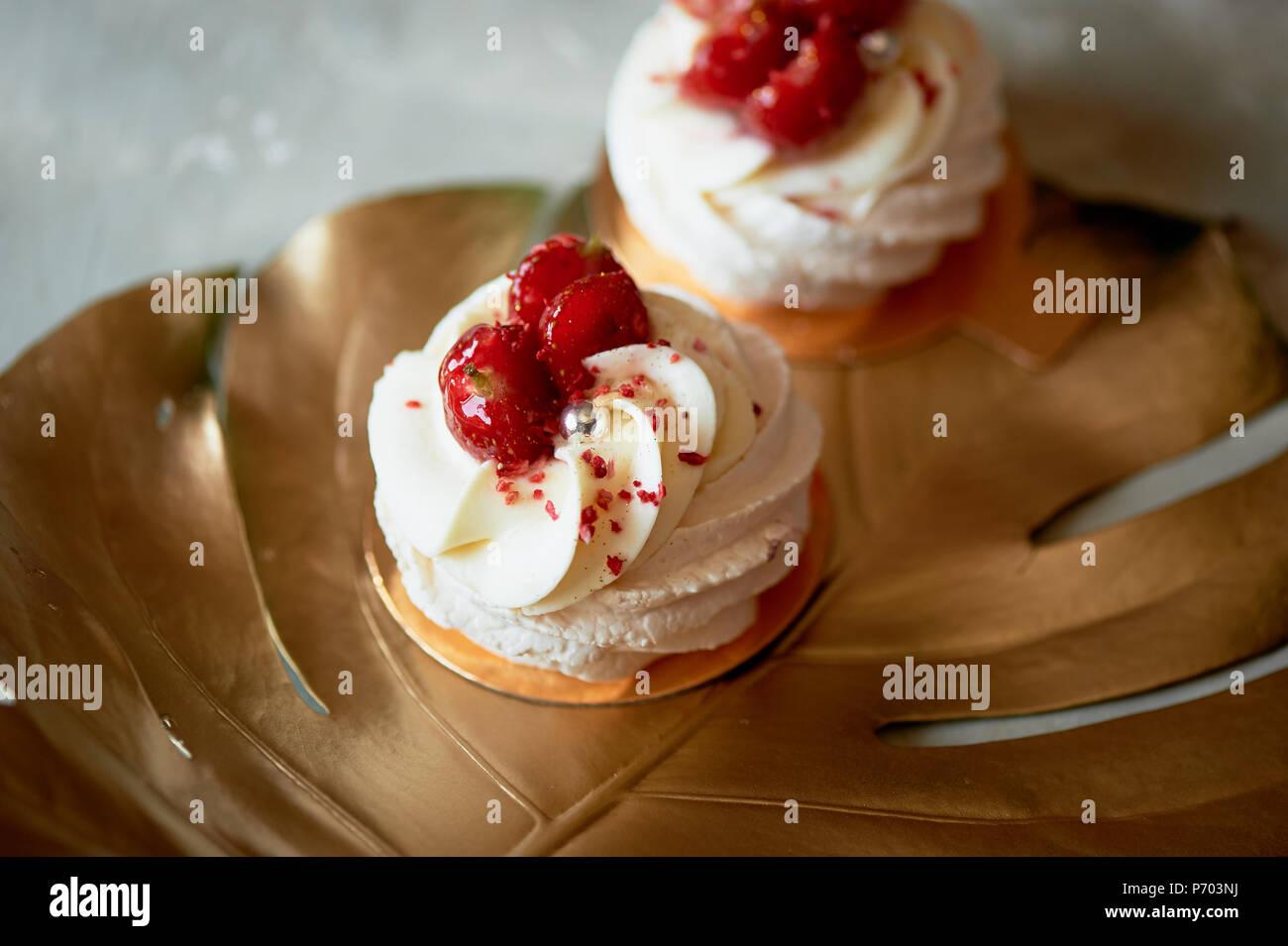 Luftig und köstliche meringue Anna Pavlova auf einem Blattgold monstera. Kulinarische Kunst Stockbild