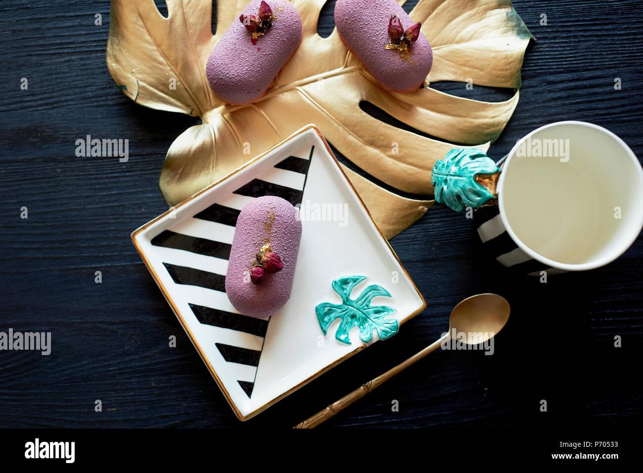 Lila Früchte Mousse Cake, auf einer schönen Untertasse. Auf einem dunklen Hintergrund, mit einem Blatt monstera in gold Lack lackiert. Kulinarische Kunst Stockfoto