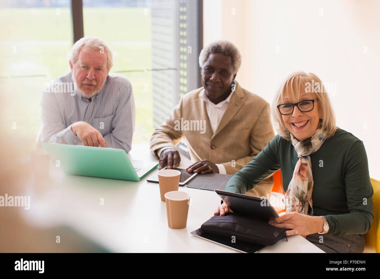 Lächelnd Senior Business Nutzer digitaler Tabletten und Laptop im Konferenzraum treffen Stockbild