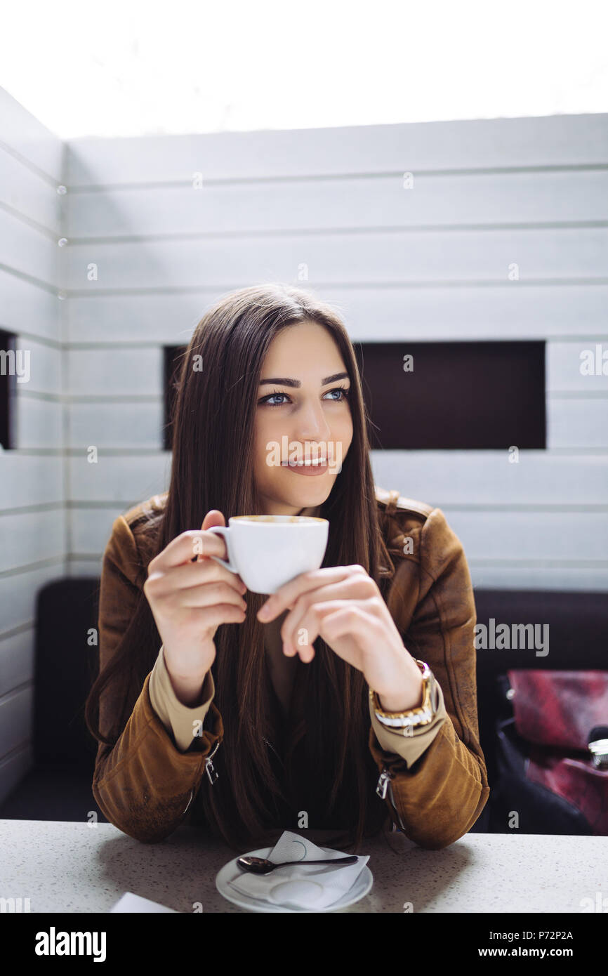 Hübsche Brünette junge Frau im Cafe Bar und trinken Kaffee sitzen. Stockbild