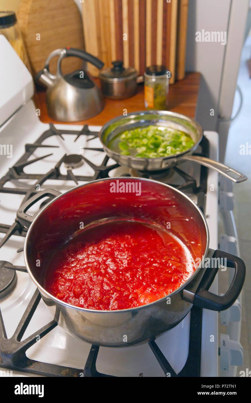kochen einen topf mit roter tomatenso e und eine pfanne mit paprika auf einem gasherd und ein. Black Bedroom Furniture Sets. Home Design Ideas
