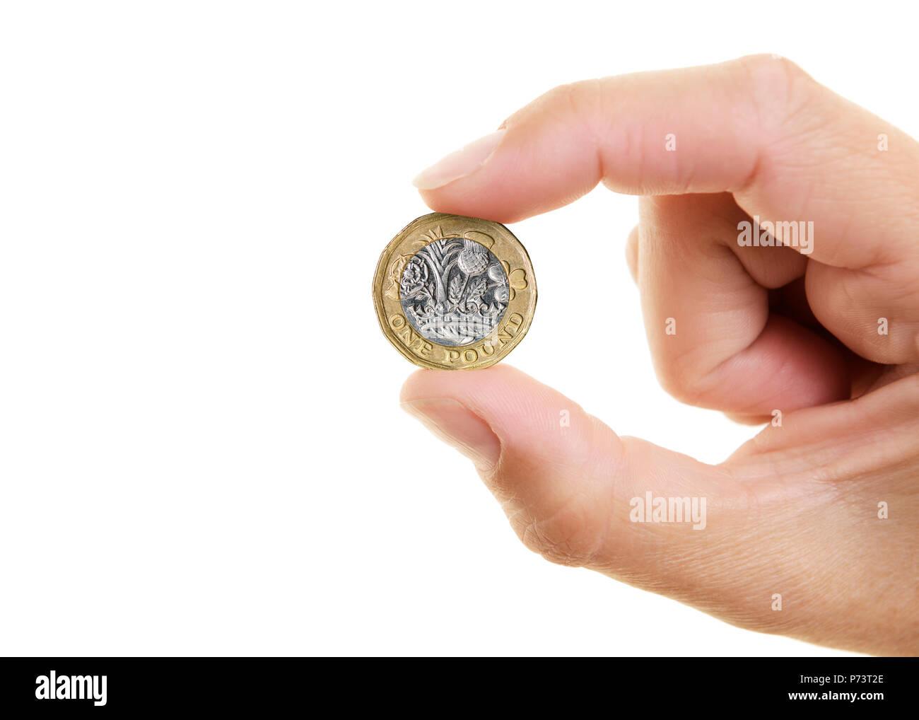 Neue Pound Münze statt zwischen den Fingern von Womans Hand, Ausschneiden Stockbild
