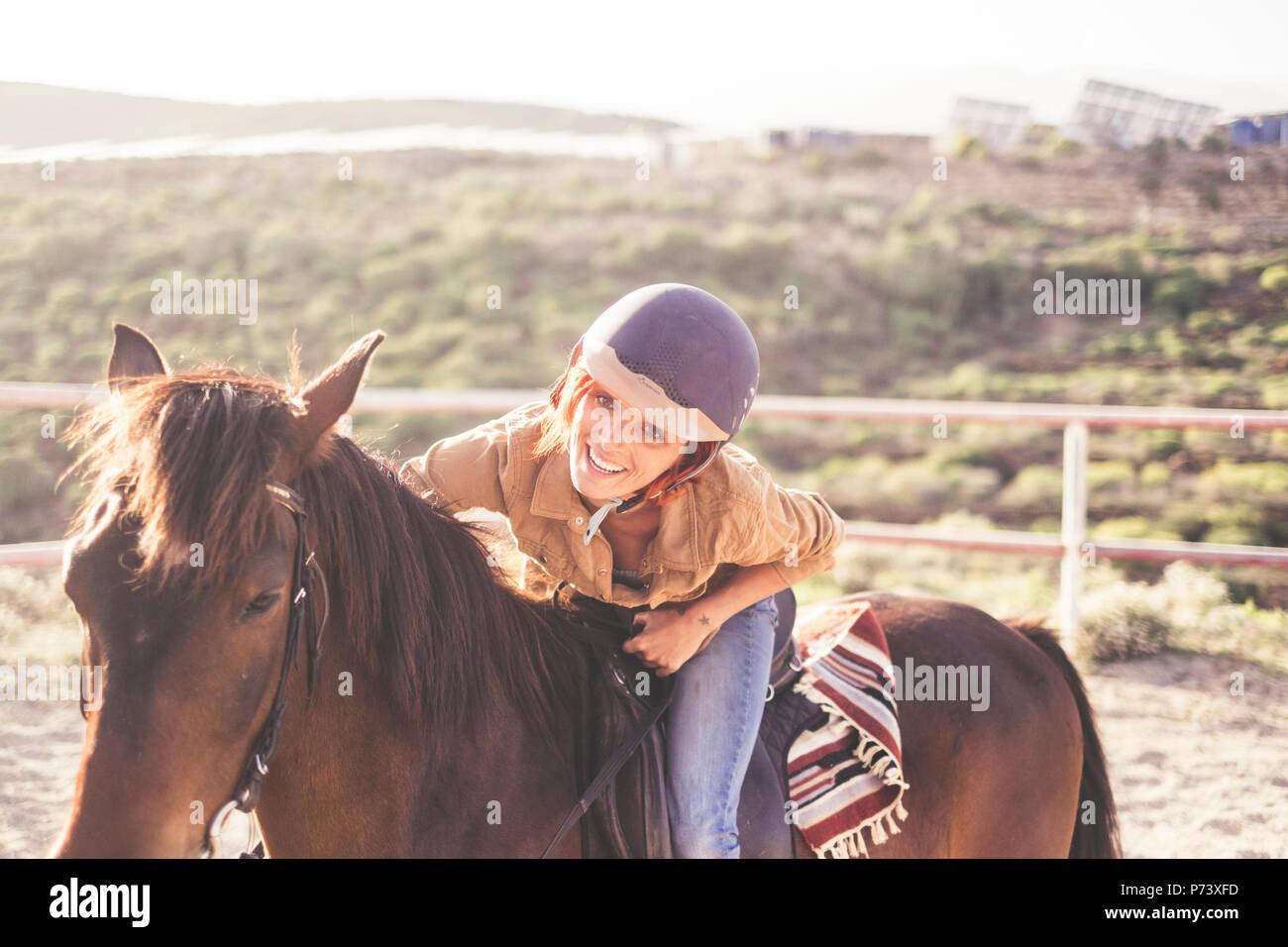 Fahrt mit einem Helm für eine schöne attraktive junge Frau mit schönen Lächeln. Jeans und Freizeitkleidung für Mädchen in der Freizeit mit braunen h Stockbild