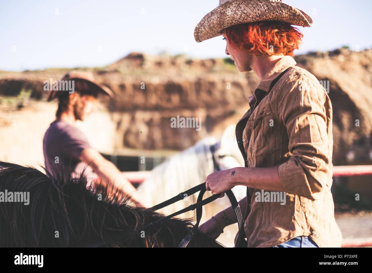 Paar der Moderne cowboy Ride zusammen. ein Mann und eine Frau mit zwei Pferde. warm filter Bild für alternativen Lebensstil und arbeiten oder Aktivitäten im Freien Stockbild