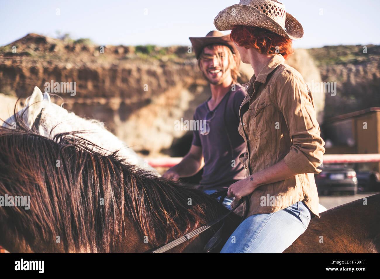 Paar Leute und ein paar Pferde haben freizeitaktivität zusammen in die Landschaft. modernen Lebensstil, der aus dem Amt und natürliche Art und Weise zu leben und en Stockbild