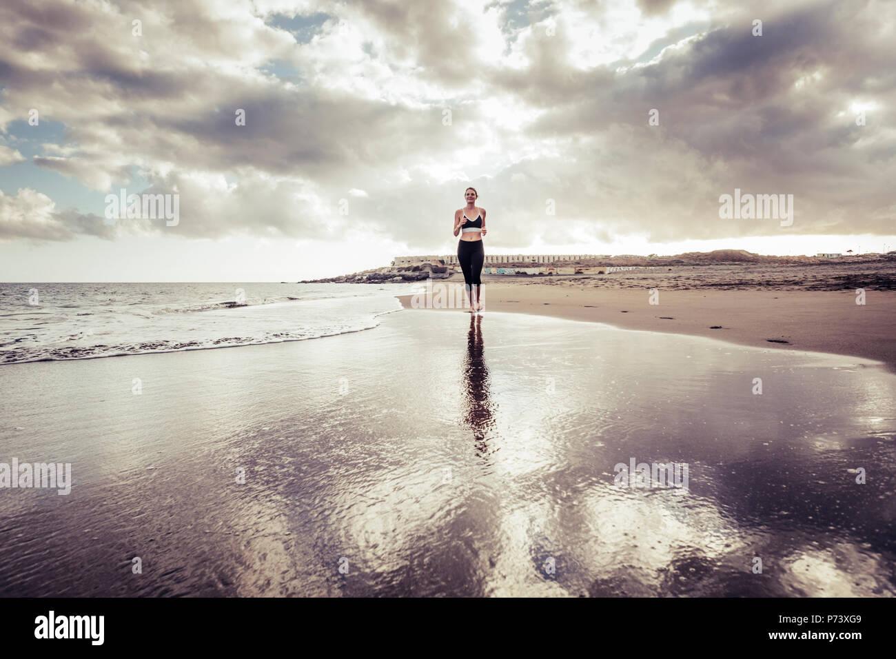 Lonely runner Dame jungen kaukasischen Mädchen am Strand barfuß Stil läuft am Ufer. Wellen und Meer Sport Konzept. Sonnenuntergang ein Stockbild
