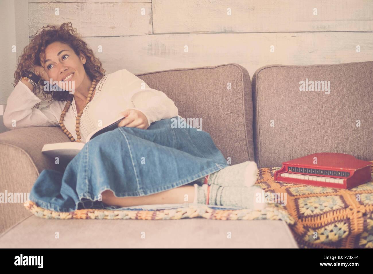 Schöne kaukasische Frau legte sich entspannt auf dem Sofa zu Hause sucht außerhalb des Fensters. kleine Pianobar Spielzeug zu ihren Füßen. Kreativität Gefühl für schönes Stockbild