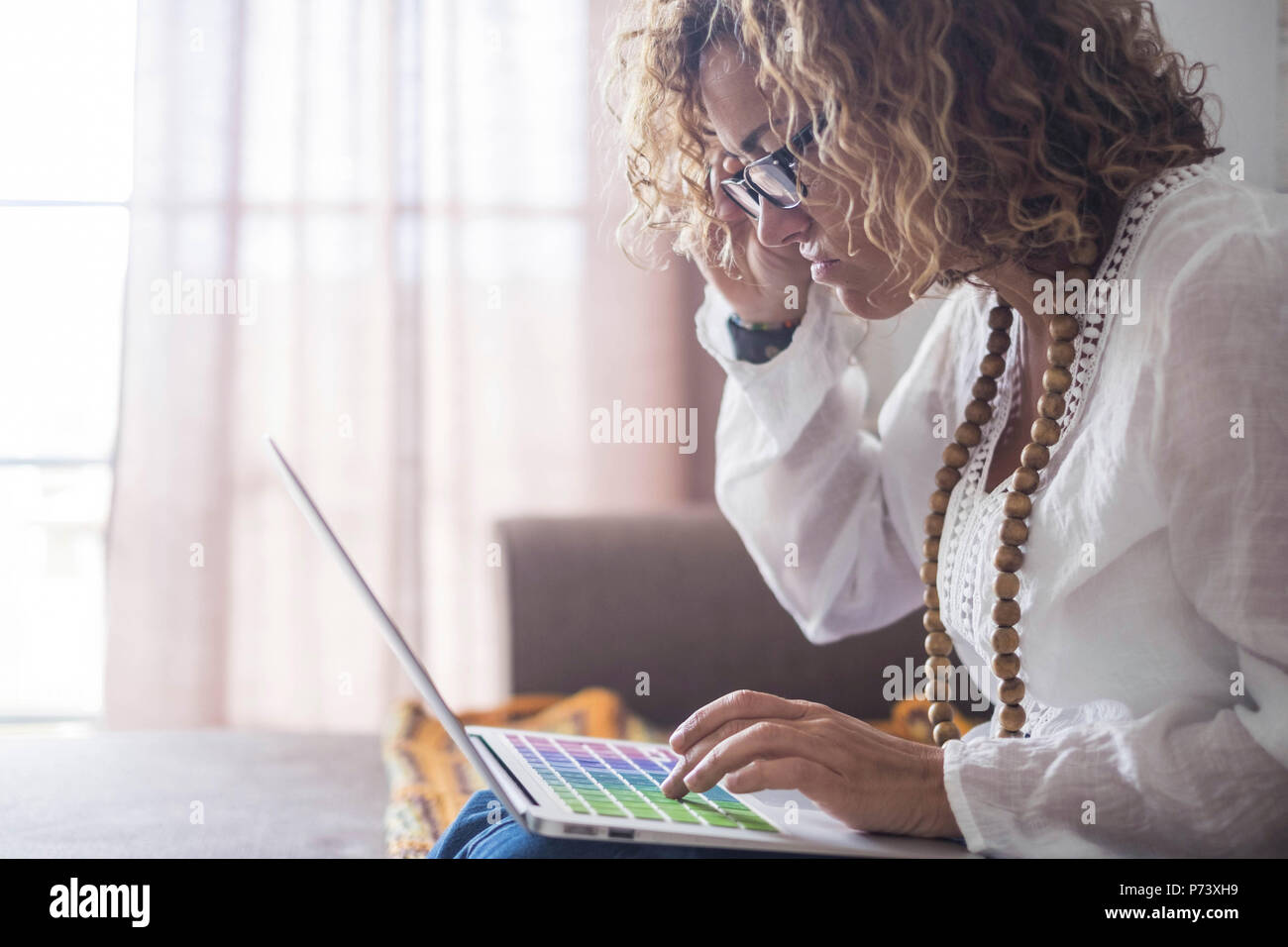 Unglücklich und hässliche Schöne kaukasische Frau auf Laptop zu Hause arbeiten. Alternative office Konzept für Menschen leben in Freiheit Lifestyle. farbige Comput Stockbild