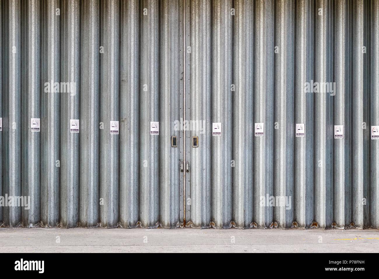 Schiebetüren und Falttüren industrielle Türen mit Rauchverbotsschilder, eine Ladestation für Lkw auf einer Straße von London City Stockbild
