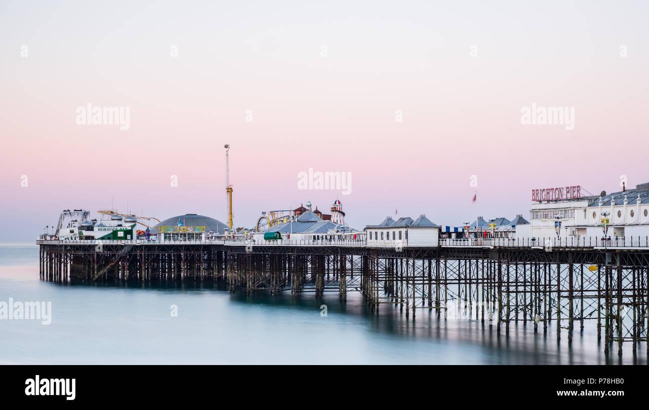 Brighton Pier (Central Pier) in Brighton, East Sussex, bei Sonnenaufgang mit farbenfrohen Pastelltönen in einem wolkenlosen Himmel und Reibungs- und blaues Wasser Stockbild