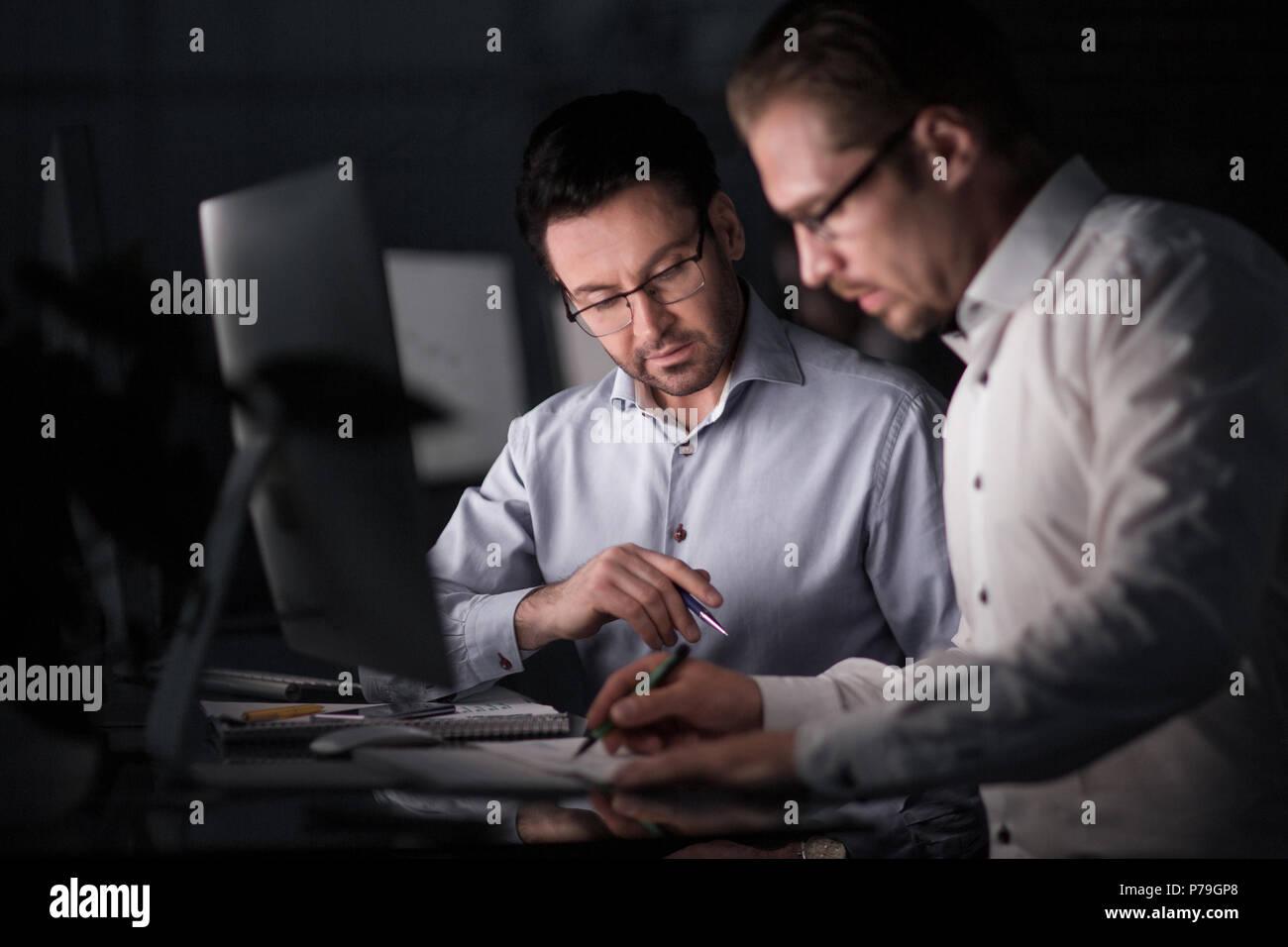 Die Kollegen arbeiten mit Dokumenten in den Abend. Stockbild