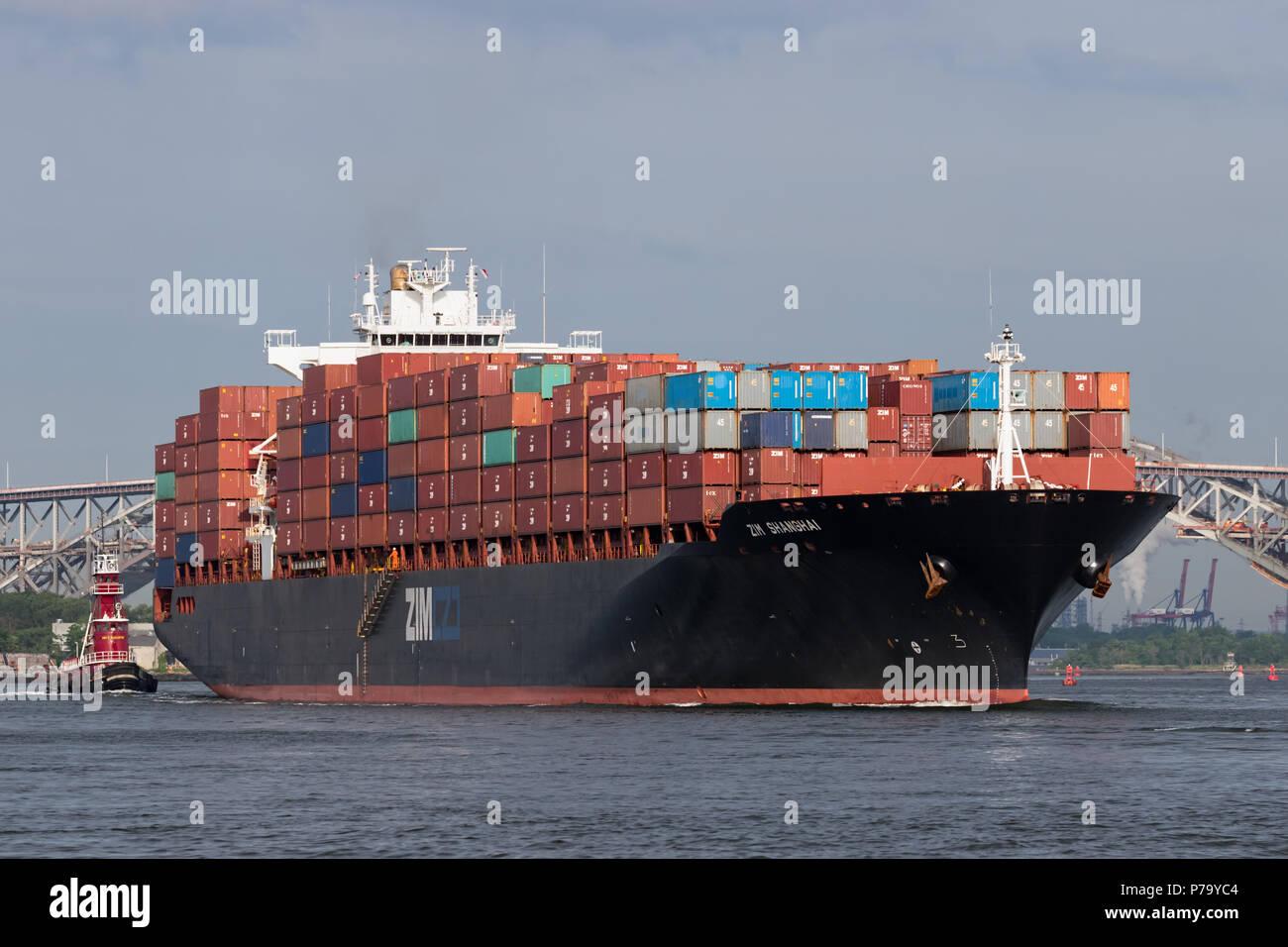 Das containerschiff ZIM Shanghai der ausgehende Port Elizabeth für den New Yorker Hafen, Bayonne Bridge und Newark Bay in der Ferne. Stockfoto