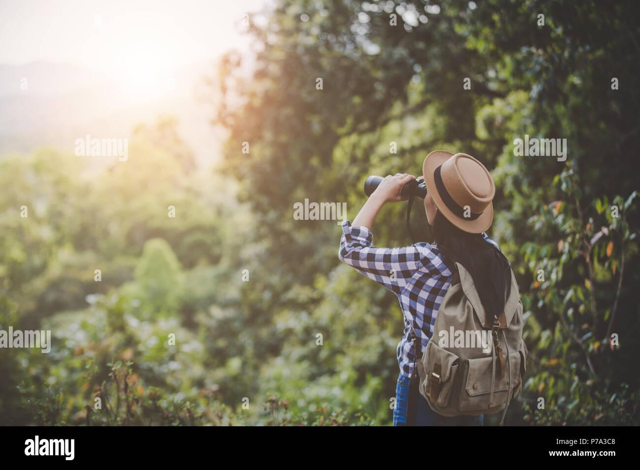 Frau mit fernglas und teleskop im regenwald travel concept