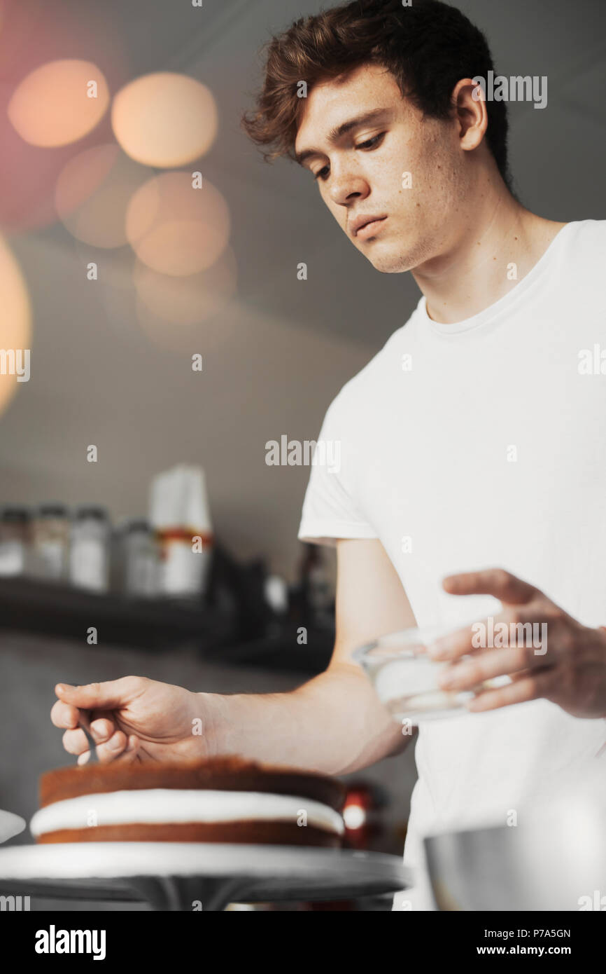 Jungen attraktiven Mann Backen Schokolade Kuchen mit Buttercreme. Stockbild