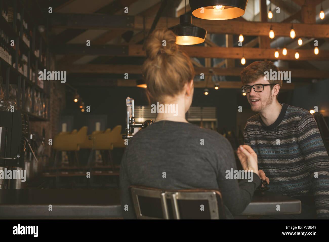 Paare, die miteinander sprechen, an der Theke Stockbild
