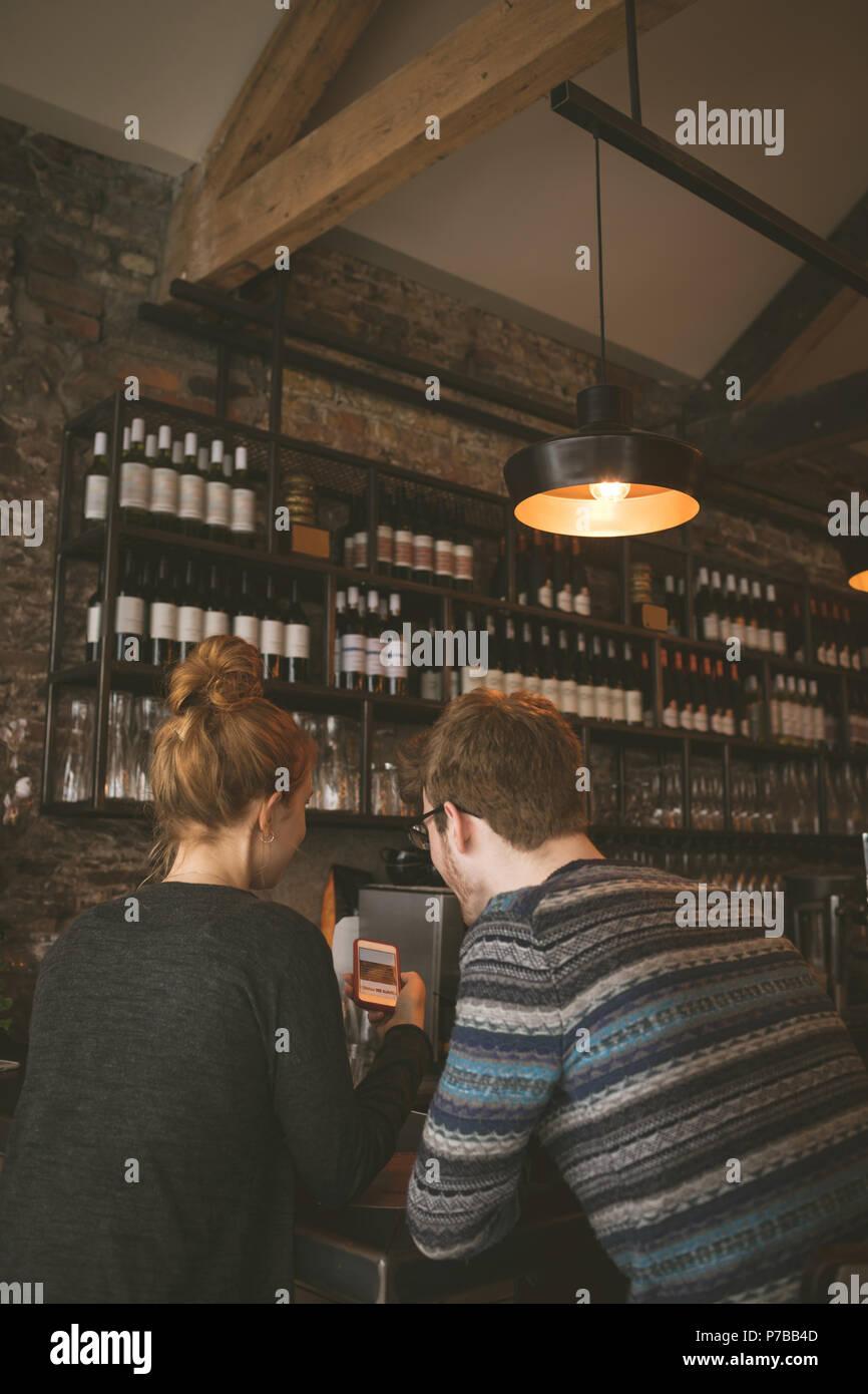 Paar am Handy im Restaurant suchen Stockbild