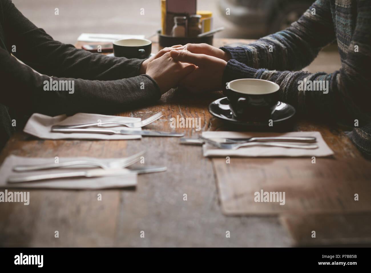 Paar Hände halten im Cafe Stockbild