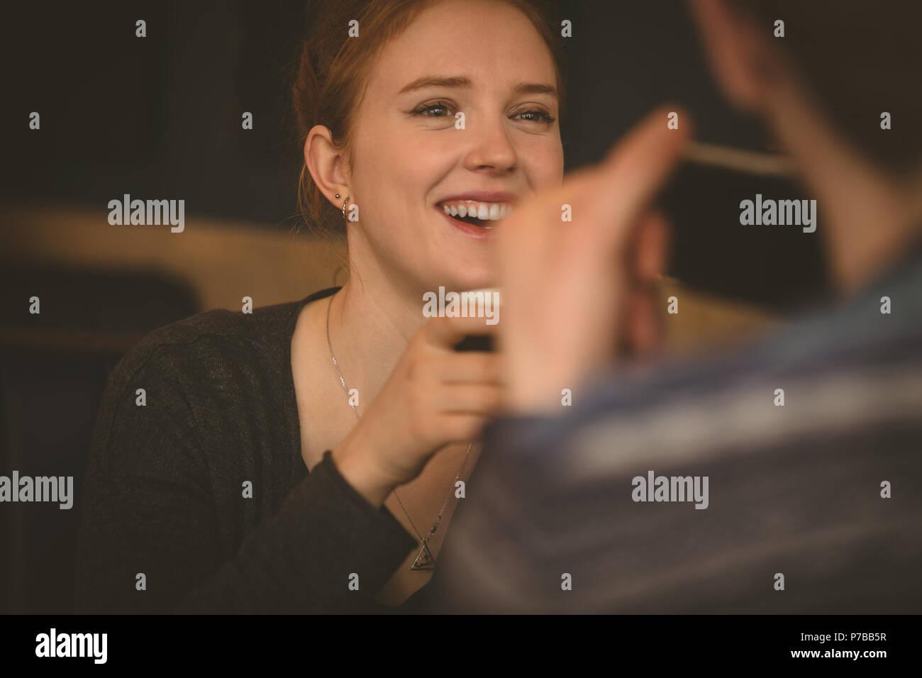 Lächelnde Paare miteinander sprechen, im Restaurant Stockbild