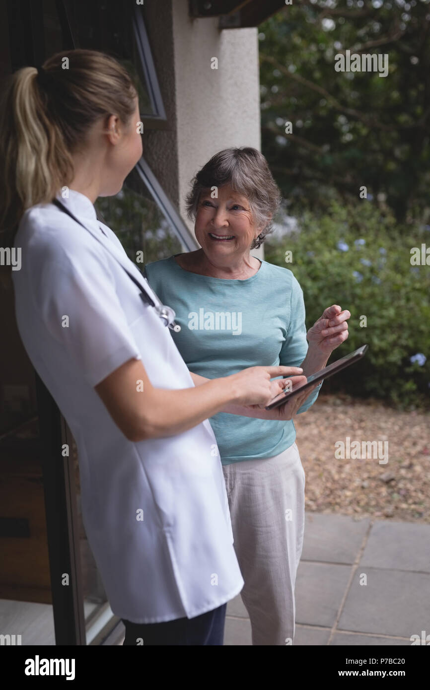 Physiotherapeut und ältere Frau mit einem Tablet Stockfoto