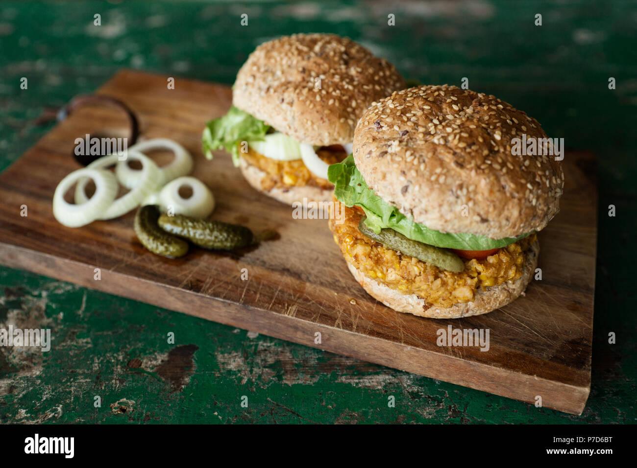 Vegane Burger mit Mais pattie, Essiggurken und Zwiebeln, essen Noch-leben, Studio shot Stockbild