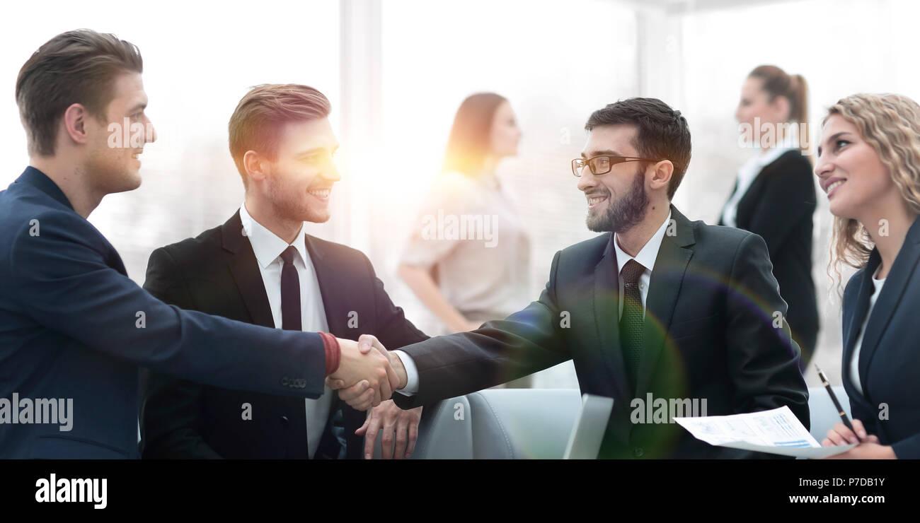 Partner Geschäft abzuschließen und Händeschütteln im Beisein von Teammitgliedern Stockbild