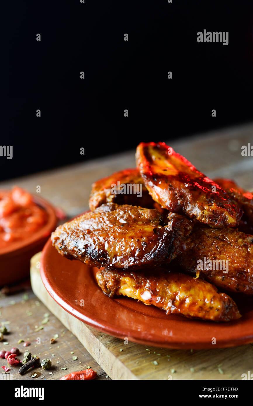 Nahaufnahme von einigen barbecue Chicken Wings in einem Steingut Teller und eine Schüssel mit Barbecue Sauce auf einem rustikalen Holztisch, vor einem schwarzen Hintergrund wit Stockfoto