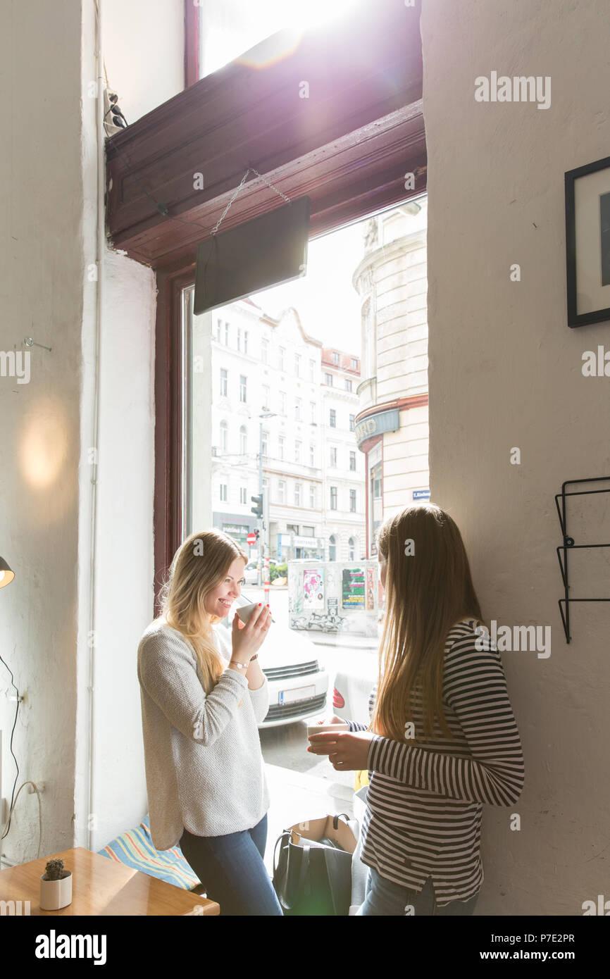 Junge Frauen über Kaffee im Cafe chatten Stockbild