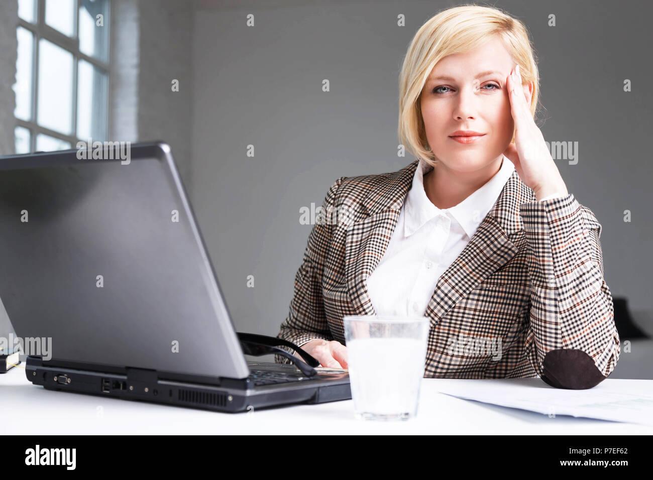 Blond Geschäftsfrau stilvollen Anzug haben Kopfschmerzen, mit brausetabletten Pille auf Wasser im Glas, Arbeitsplatz mit Laptop in Weiß Büro Stockbild
