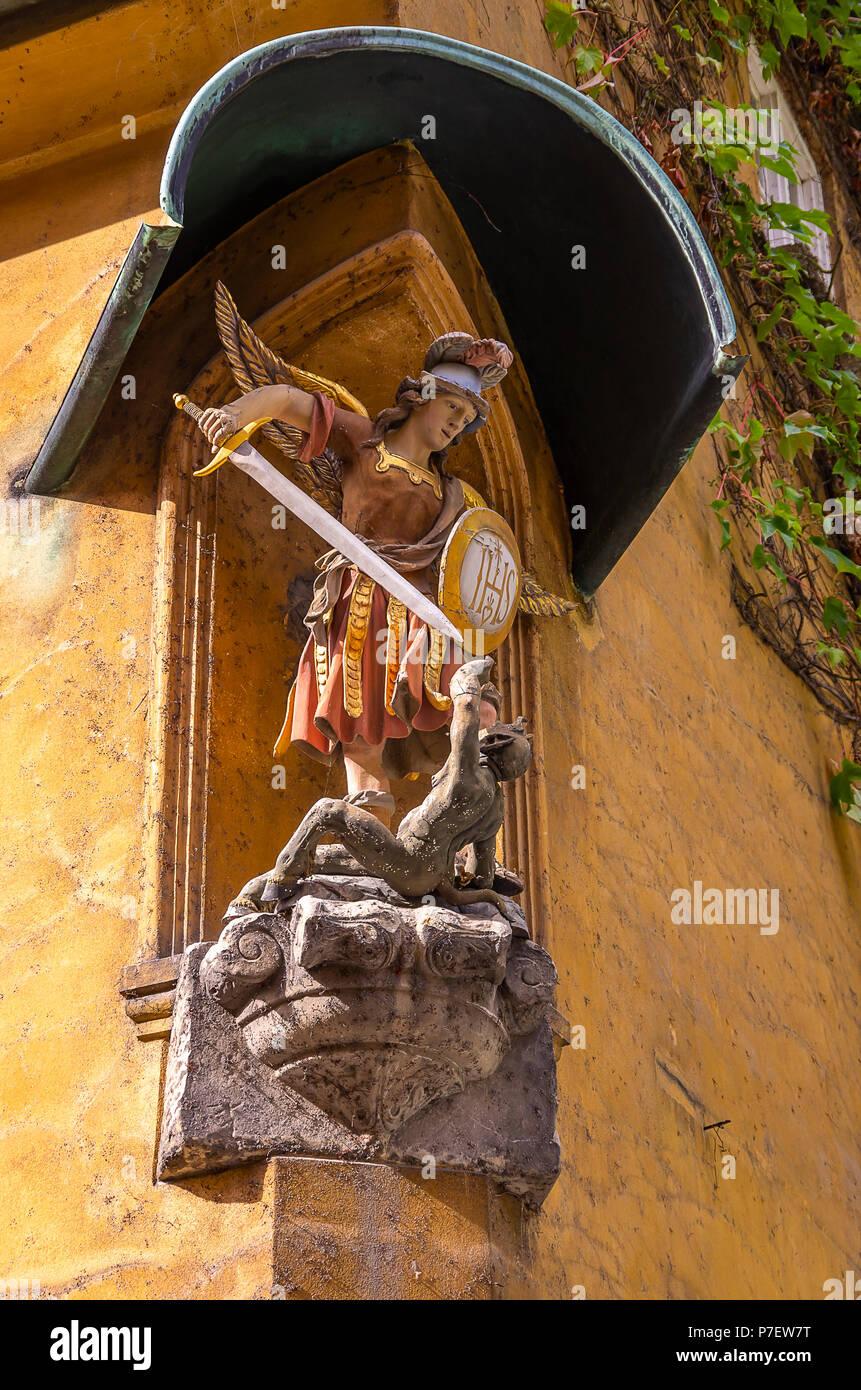 Fuggerei, Augsburg, Bayern, Deutschland - Darstellung des Erzengels Michael im Kampf gegen die Teufel an der Ecke eines Hauses. Stockfoto