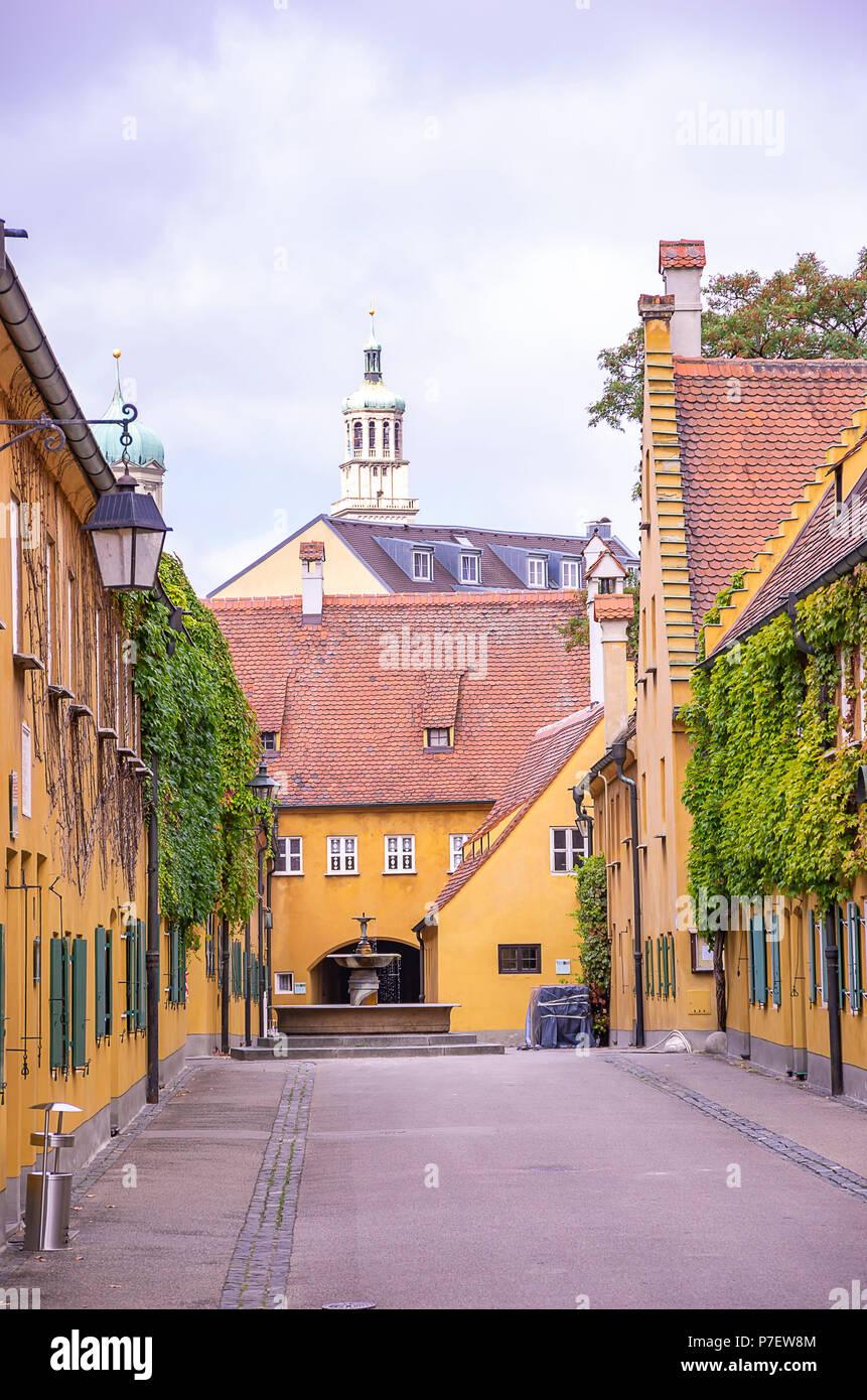 Fuggerei, Augsburg, Bayern, Deutschland - Blick durch die Mittlere Gasse Gasse zu den Brunnen und den Perlachturm Tower. Stockfoto