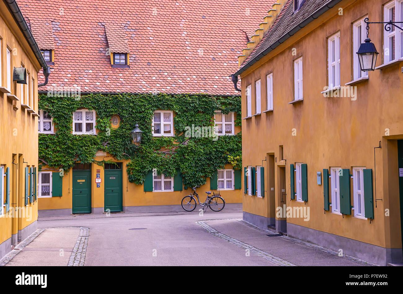 Fuggerei, Augsburg, Bayern, Deutschland - Blick durch eine der Gassen mit den armenhäusern. Stockfoto