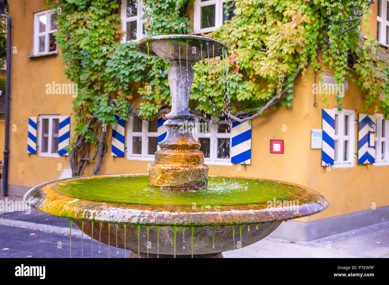 Fuggerei, Augsburg, Bayern, Deutschland - Zentrale Becken gut in der Herrengasse Gasse. Stockfoto
